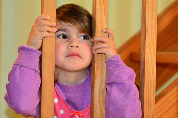 A photo of a young, anxious looking girl peering through the bars of the stairs