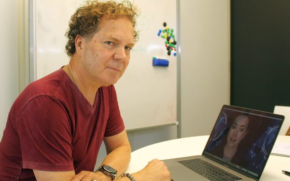 "Greg Cross of Soul Machines sits in front of a laptop with the image of the digital human  ""Rachel"" on screen"