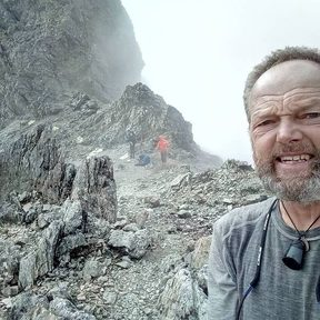 High up in Waiau Pass, Bruce pauses for a selfie in the background, two other walkers are climbing a steep, rocky ridge.