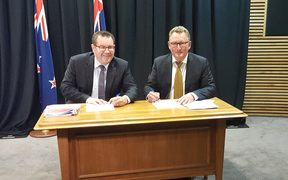 Finance Minister Grant Robertson and RBNZ governor designate Adrian Orr sign a new policy agreement.