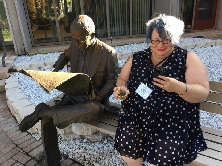 RNZ's acting Digital Editor, Megan Whelan sitting next to a statue of Nelson Poynter.