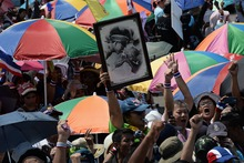 A protester holds a picture of King Bhumibol Adulyadej during Saturday's rally.