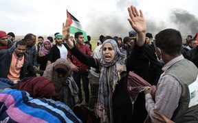 Palestinian protesters wave their national flag and gesture during a demonstration commemorating Land Day near the border with Israel, east of Khan Yunis, in the southern Gaza Strip.
