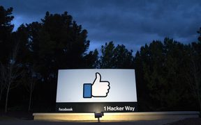 A lit sign is seen at the entrance to Facebook's corporate headquarters