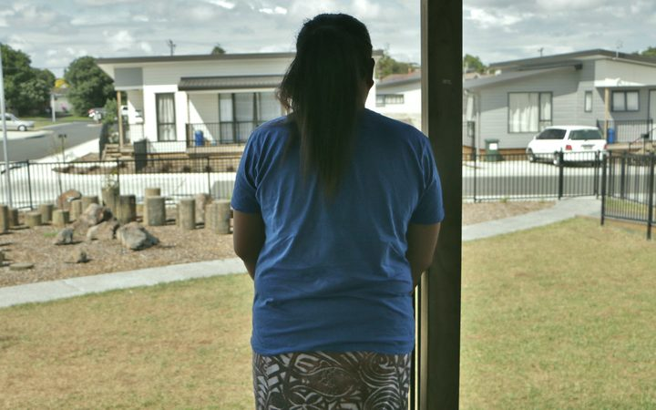 Maria looks out over the temporary accommodation she calls home for now.