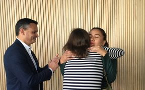 Julie-Anne Genter hugs Marama Davidson while James Shaw looks on