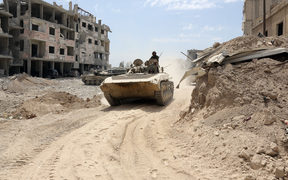 A picture taken on April 8, 2018, shows Syrian Army soldiers advancing in an area on the eastern outskirts of Douma.