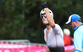 New Zealand's Samuel Gaze gestures in the transition area after suffering a puncture.