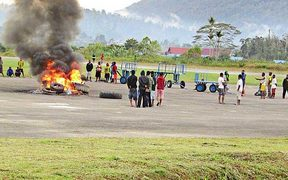 A group of angry residents set tires on fire at Oksibil Airport in Pegunungan Bintang regency, Papua, on November 18, 2017.