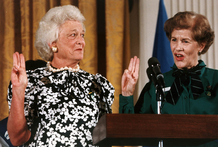 First Lady Barbara Bush gives the Girl Scout salute as she is invested as the 14th national honorary president of the Girl Scouts/USA by the organiztion's former national president Betty Pilsbury on 28 June 1989.