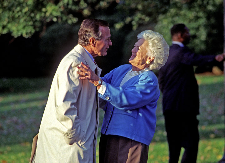 United States President George H.W. Bush hugs first lady Barbara Bush as he departs the South Lawn of the White House in Washington, DC in 1992.