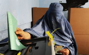 An Afghan woman casts her ballot at a polling station in the northwestern city of Herat.