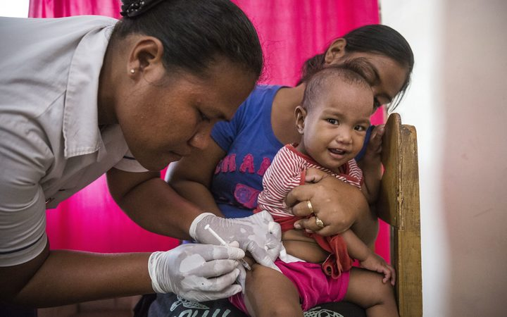 Taratiteiti Kirition holding her 1-year-old daughter Pepeeti while a nurse gives her an immunisation shot at a Kiribati clinic