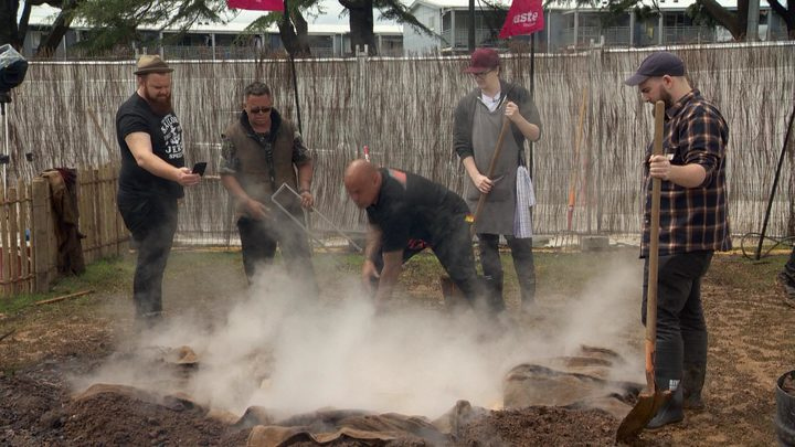 Rewi Spraggon, centre, guides chefs in the art of hangi making.