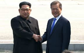 North Korea's leader Kim Jong Un (L) and South Korea's President Moon Jae-in shake hands at the Military Demarcation Line that divides their countries at Panmunjom.