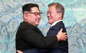 North Korea's leader Kim Jong Un (L) and South Korea's President Moon Jae-in (R) hug during a signing ceremony near the end of their historic summit