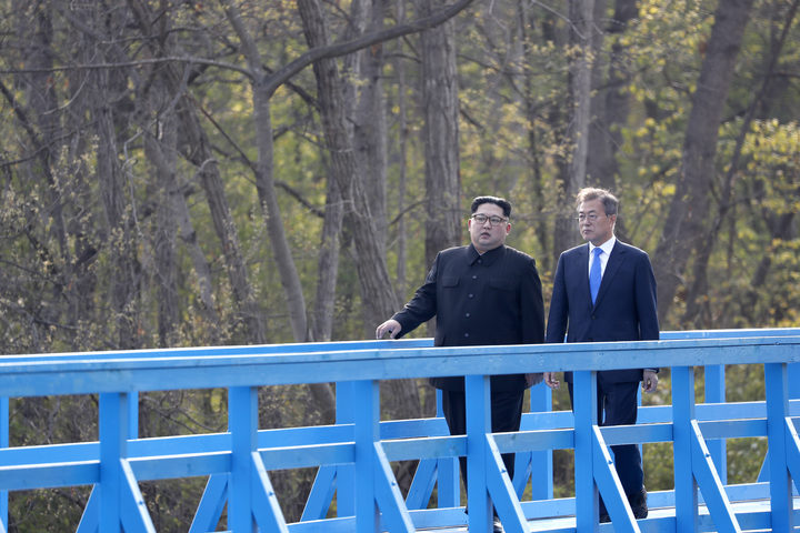 North Korea's leader Kim Jong Un (L) and South Korea's President Moon Jae-in (R) walk on a bridge after a tree-planting ceremony at the truce village of Panmunjom