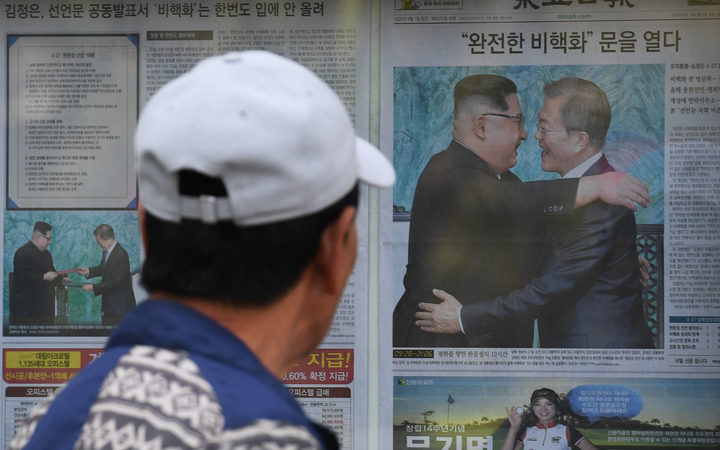 A man walks past a newspaper featuring a front page story about the summit between South Korean President Moon Jae-in and North Korean leader Kim Jong Un