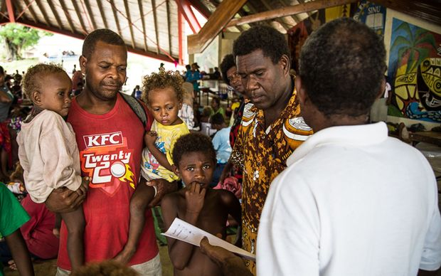 Families shelter at a Honiara evacuation centre.