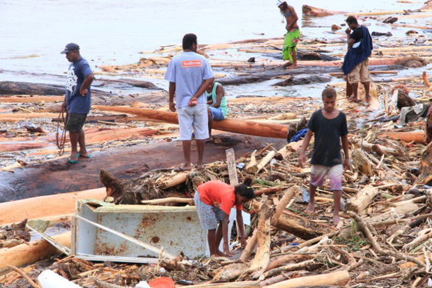 People search the rubble left by flooding in the Solomon Islands.