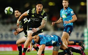Blues midfielder Sonny Bill Williams, bottom, and Hurricanes wing Ben Lam keep their eyes on the ball.