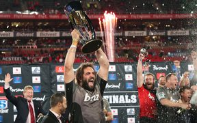 Crusaders captain Sam Whitelock holds the Super Rugby trophy aloft after their championship win last year.