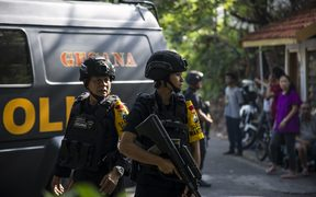 Indonesian police officers patrol outside a church following a suicide bomb in Surabaya.