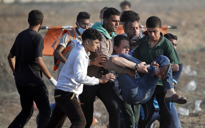 Palestinians carry away an injured protester who was shot in his leg during clashes with Israeli forces east of Gaza City.