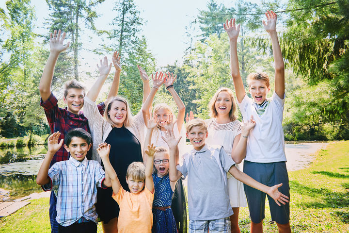 A photo of happy brothers and sisters  raising arms in the park