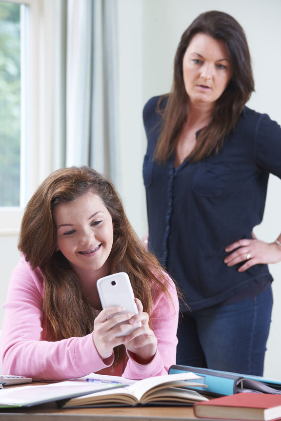 A photo of a teenage daughter using her mobile phone whilst studying. Her mother can be seen looking on angrily from behind.