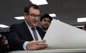 Grant Robertson looking over the first print of his first budget.