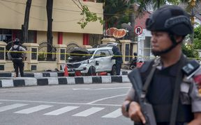 Police stand guard as a car that was used to attack the police headquarters is examined in Pekanbaru on May 16, 2018.
