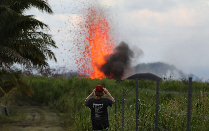 A man takes a photo of a lava fountain from a Kilauea volcano fissure on Hawaii's Big Island
