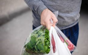 Man carrying plastic bag in his hand after shopping. Closeup of bag full of fruits and vegetables.