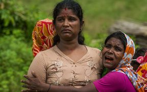 File photo, taken on September 27, 2017, of Hindu women crying near the dead bodies of their family members in Ye Baw Kyaw village, Maungdaw in Myanmar's northern Rakhine state.