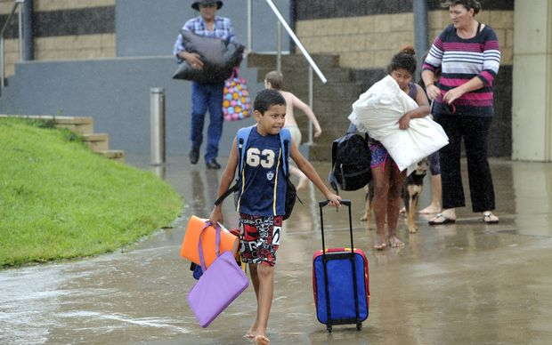 Families leave the Cooktown evacuation centre after taking shelter overnight.