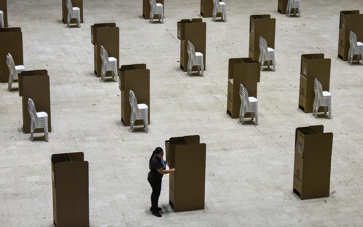 A worker assembles voting booths at a polling station in Cali, Colombia