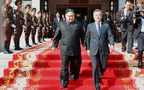 South Korea's President Moon Jae-in (R) and North Korea's leader Kim Jong Un (L) walking together after the summit at the north side of the truce village of Panmunjom in the Demilitarized Zone dividing the two Koreas.