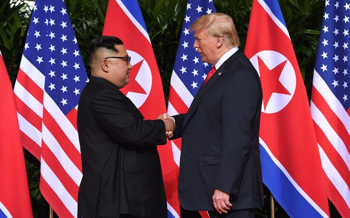 North Korea's leader Kim Jong Un shakes hands with US President Donald Trump at the start of their historic US-North Korea summit at the Capella Hotel on Sentosa island in Singapore