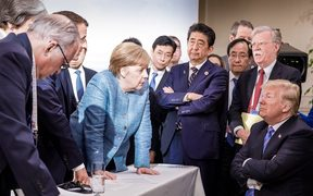 US President Donald Trump, right, talking with German Chancellor Angela Merkel and surrounded by other G7 leaders.