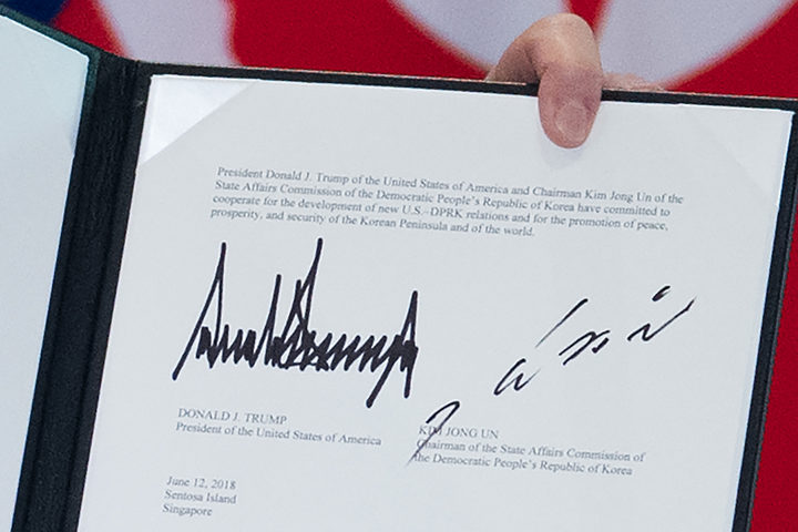The signatures of US President Donald Trump and North Korea's leader Kim Jong Un on a document held up by Trump following a signing ceremony during their historic US-North Korea summit
