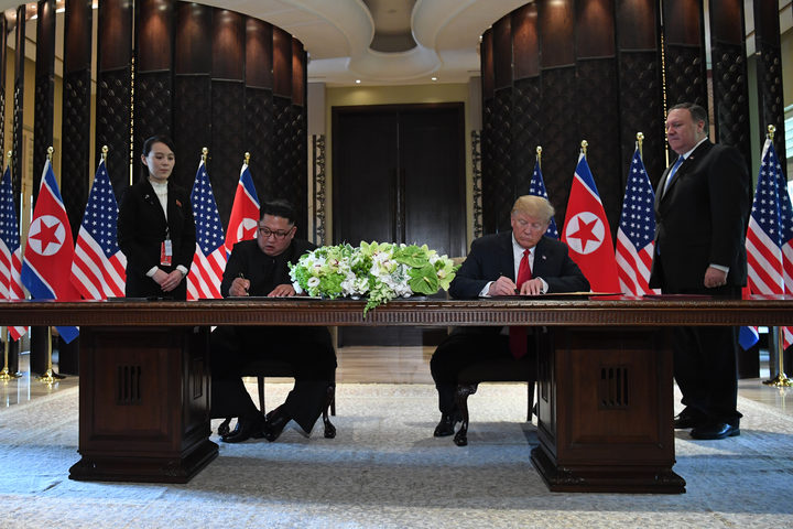 US President Donald Trump and North Korea's leader Kim Jong-un sign documents after the summit meeting.
