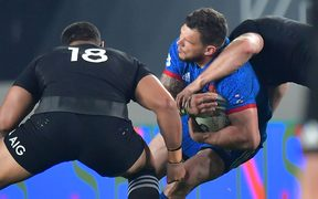 France's Remy Grosso is tackled by All Blacks Ofa Tu'ungafasi and Sam Cane.