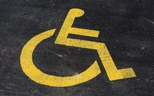 Yellow wheelchair symbol in parking space.