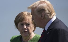 German Chancellor Angela Merkel confers with US President Donald Trump.
