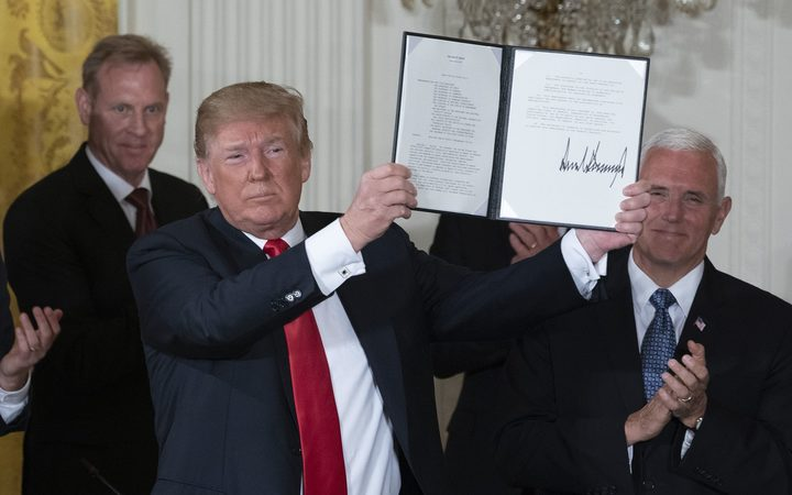 United States President Donald Trump displays Space Policy Directive 3.