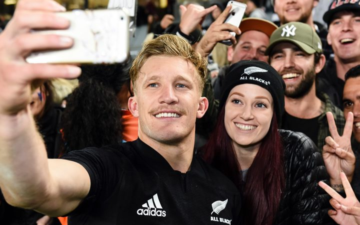 All Blacks Damian McKenzie takes a self with supporters.