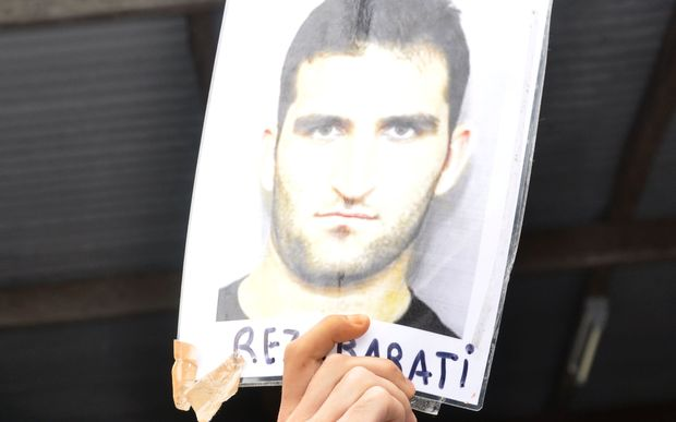 An asylum-seeker holds a picture of Reza Barati who died at the detention centre.