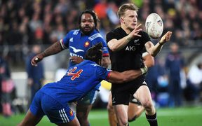 Damian McKenzie makes an offload against France.