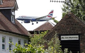 A sign in the village of Longford opposing Heathrow expansion, pictured as a British Airways aircraft prepares to land at the west London airport.